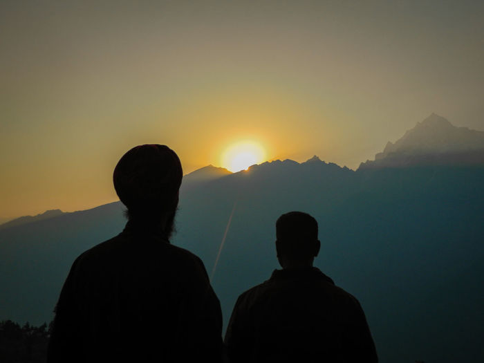 Rear view of silhouette men looking at mountain against clear sky during sunset