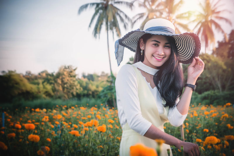 Flower garden in summer Beautiful Woman Beauty Beauty In Nature Casual Clothing Day Flower Freshness Front View Growth Happiness Hat Leisure Activity Lifestyles Nature One Person Outdoors Plant Real People Sky Smiling Standing Tree Women Young Adult Young Women