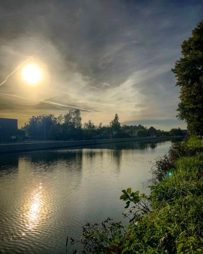 Sun setting or rising behind thick dark grey clouds over the reflecting water of a river or canal Sky Tree Water Cloud - Sky Plant Reflection Lake Beauty In Nature No People Outdoors Sunset Nature Scenics - Nature Tranquility Tranquil Scene Sunlight Sun Architecture