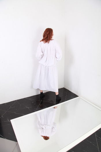 Rear view of woman standing against white wall at home