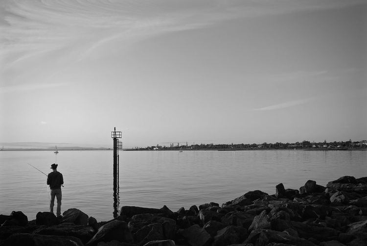 Rear view of man standing on rock and fishing at lake