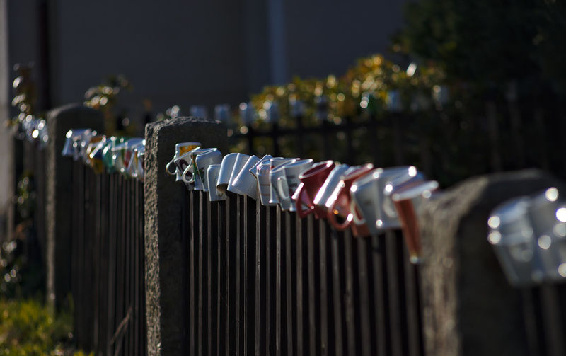 Close-up of objects hanging on metal fence