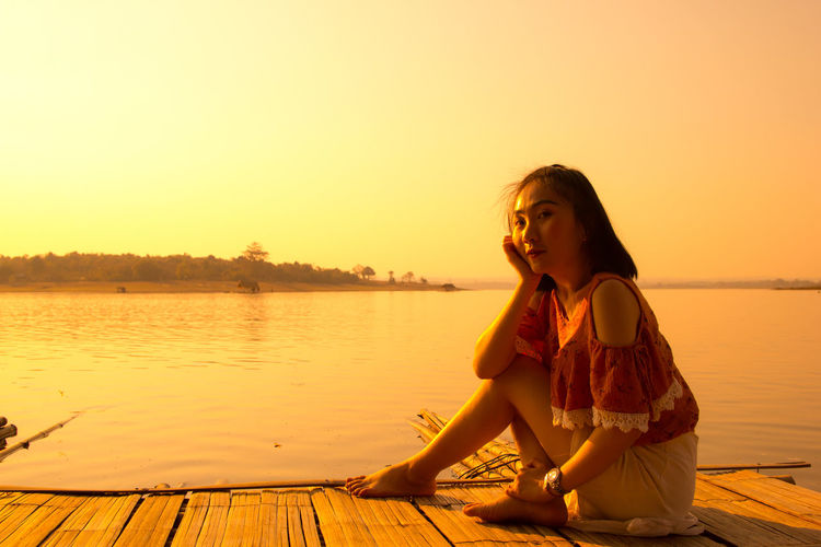 Portrait of woman sitting on wooden raft in lake against clear sky during sunset