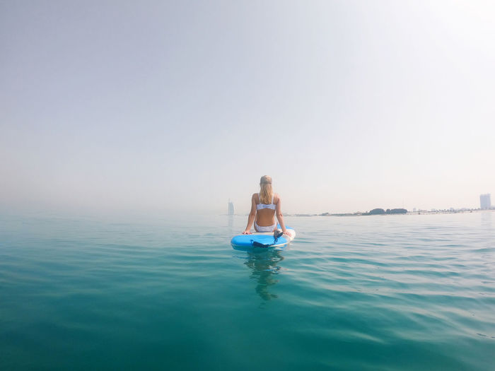 Woman sitting in sea against clear sky