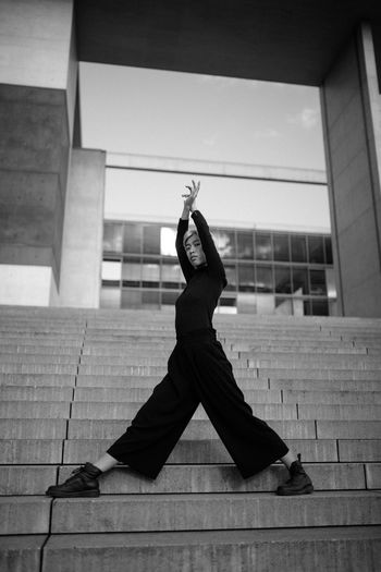 Full length portrait of woman exercising while standing on staircase against sky