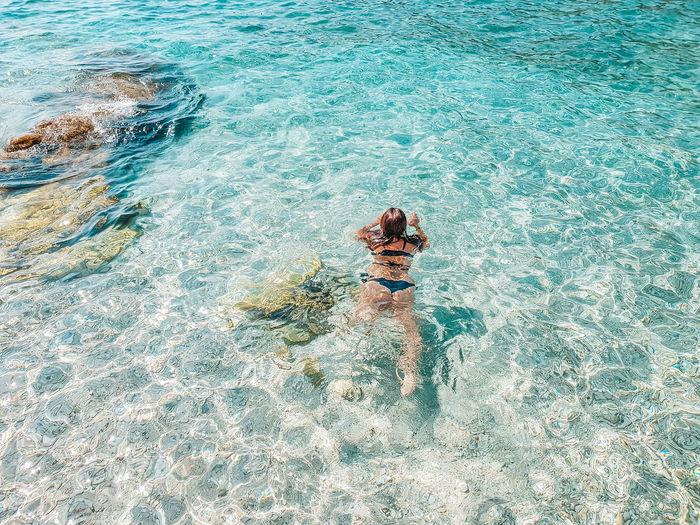 Woman in bikini swimming in crystal clear turquoise water. sea, summer, vacation.