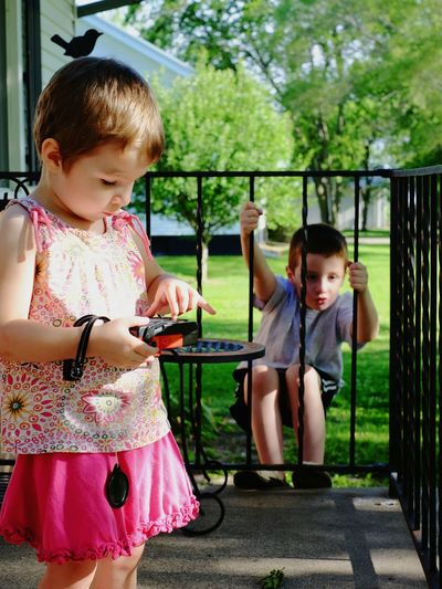 Cute Girl Playing With Toy While Brother Hanging On Railing Outside House