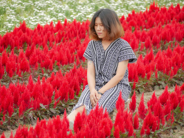 Full length of woman standing by red flowering plants