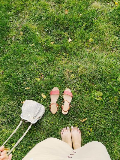 Low section of woman with sandals on field