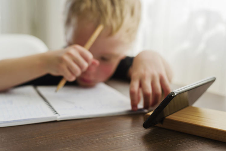 Boy doing homework while studying online through smart phone at home