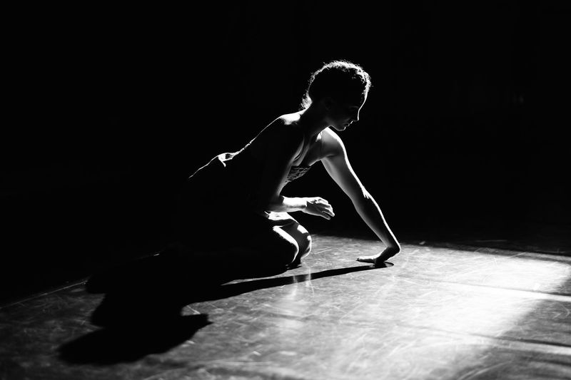 Full length of young man dancing against black background