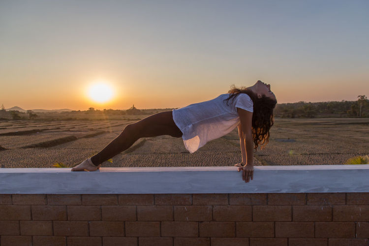 Woman with arms outstretched against sky during sunset
