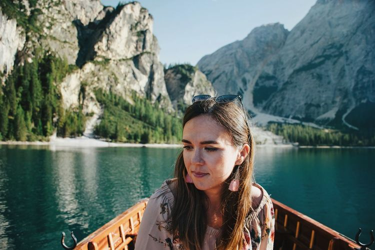 Portrait of young woman looking at lake against mountains