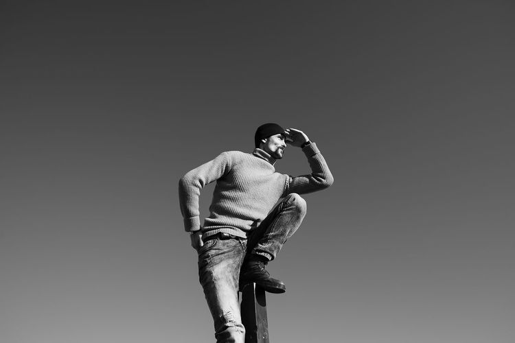 A young man does something interesting. It interacts with a wooden pile on the seashore. One person in the frame. Man on the background of a clear sky. He is warmly dressed in boots, jeans, a sweater and a hat. Casual wear. The guy wears a mustache and stubble. Hair out of the caps. Winter sunny day. Live black and white photo. Lifestyles Lifestyle Authentic Moments Authentic Candid Real People Blackandwhite Black And White Motion Rear View Looking Away Looking People People Watching people and places Space Sky Clear Sky Sweater Casual Clothing Hat Jeans Fashion Day Outdoors