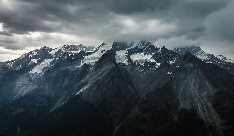 Ominous Alps Beauty In Nature Cloud - Sky Cold Temperature darkness and light Day Environment Formation Landscape Mountain Mountain Peak Mountain Range Mountain Ridge Nature Outdoors Overcast Scenics - Nature Sky Snow Snowcapped Mountain Storm Clouds Tranquil Scene Tranquility Winter EyeEmNewHere My Best Photo