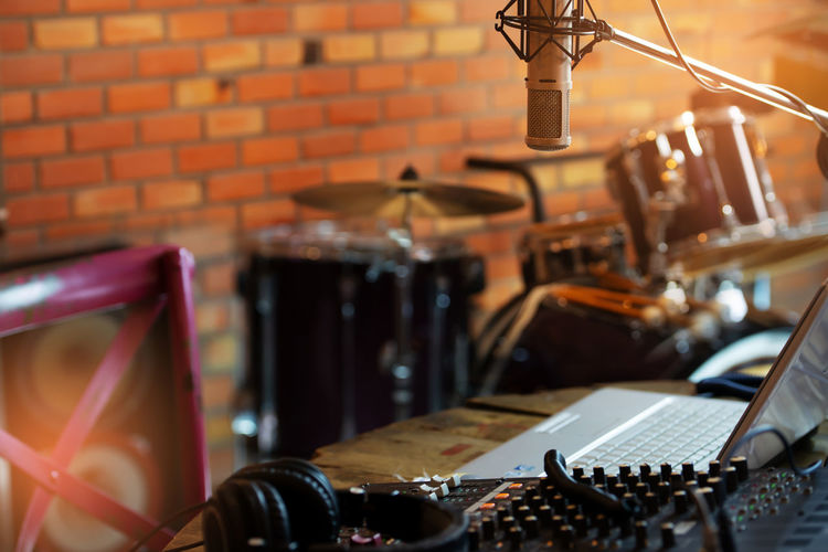 Live concert recording. Still life of digital sound recording instruments including microphone digital mixer and computer notebook with blurred drum kit in background. Laptop Computer Music Production Vintage Style Arts Culture And Entertainment Audio Equipment Condenser Mic Digital Mixer Drum Kit Focus On Foreground Indoors  Microphone Music Musical Equipment Musical Instrument Musician Life Nightlife No People Producer Professional Recording Studio Selective Focus Show Biz Sound Recording Equipment Studio Technology