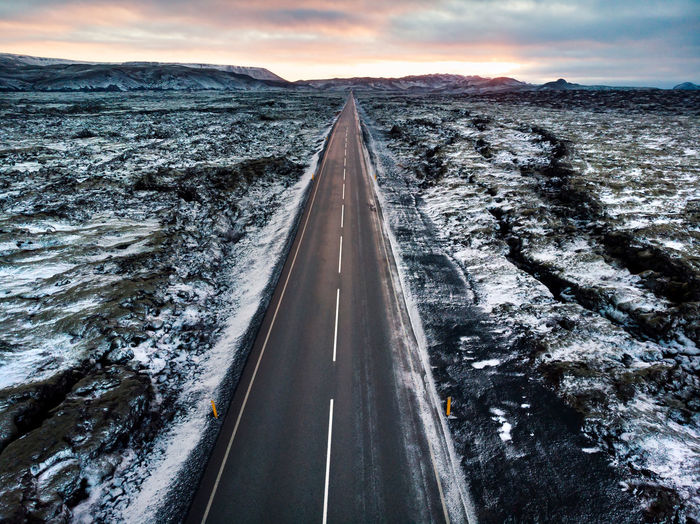 Road in Iceland surrounded by lava fields covered with snow aerial view Iceland Road Snow Lava Aerial View Transportation Sky Direction Nature The Way Forward No People Cold Temperature Cloud - Sky Diminishing Perspective Winter Sign vanishing point Motion Outdoors Beauty In Nature Landscape Travel Dividing Line Drone