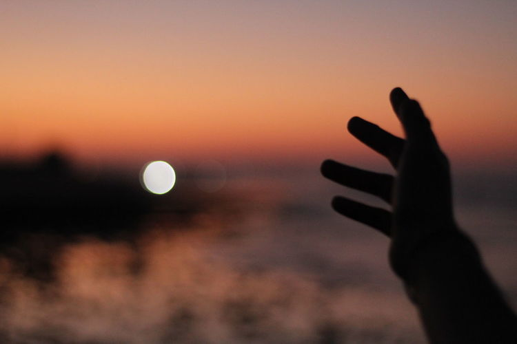 Silhouette person hand against sky during sunset
