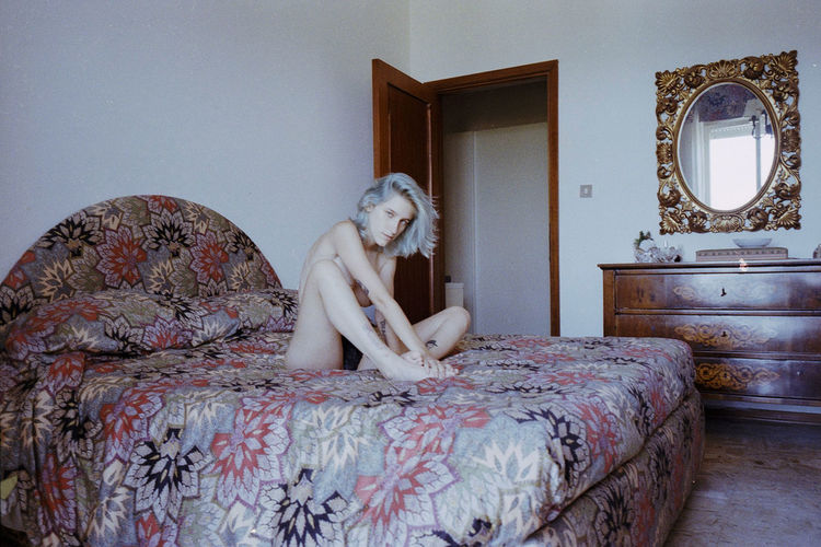 Portrait Of Topless Woman Sitting On Bed At Home