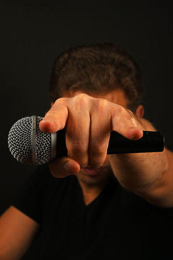Musician holding microphone while showing rock sign against black background