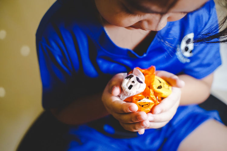 Midsection Of Girl Holding Halloween Candies