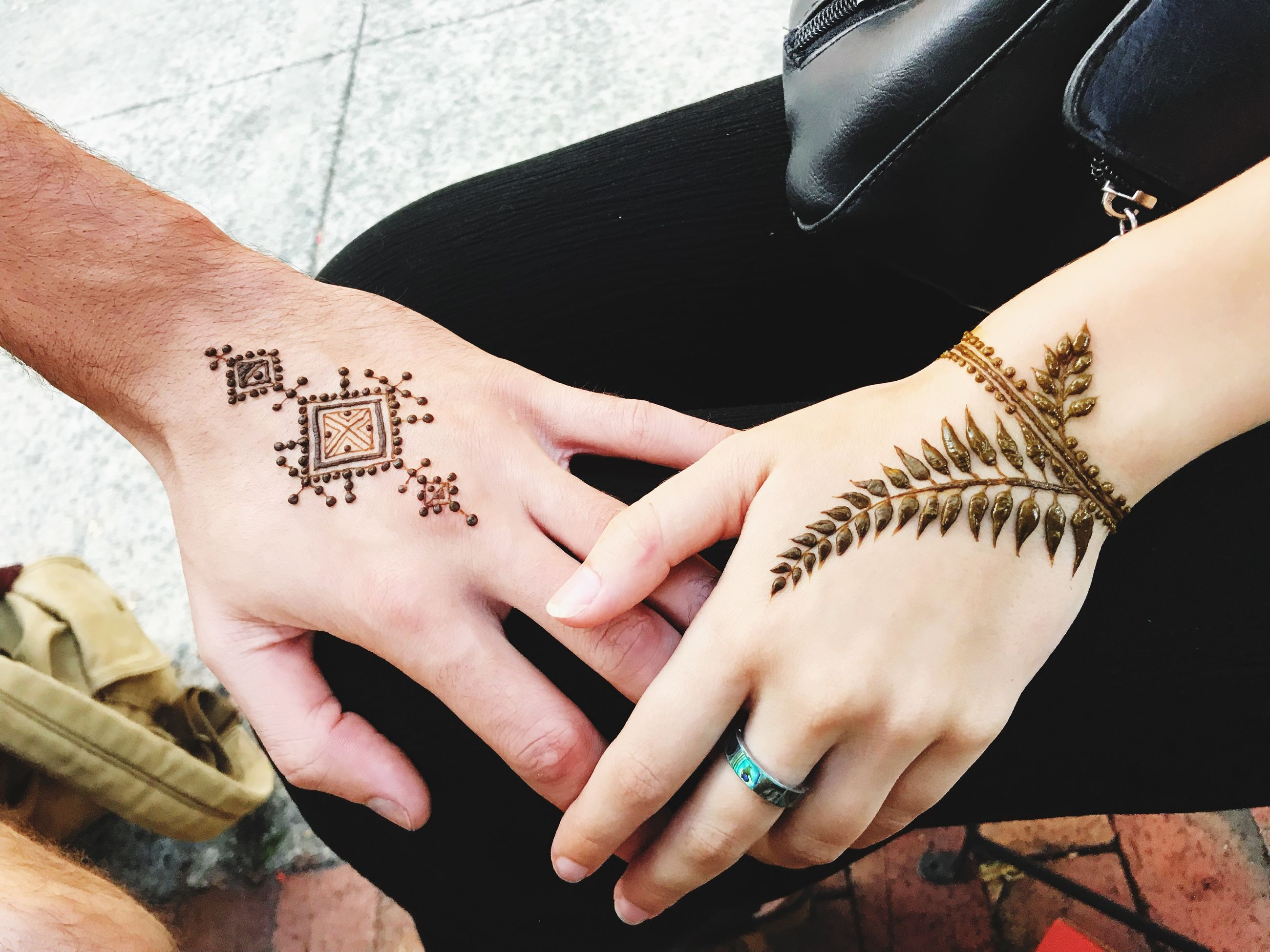 human hand, hand, real people, human body part, tattoo, high angle view, women, lifestyles, midsection, adult, indoors, henna tattoo, creativity, body part, holding, leisure activity, art and craft, finger, nail