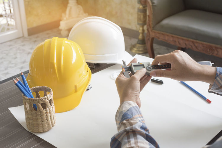 Architecture Construction Close-up Day Engineering Expertise Hardhat  Headwear Helmet Holding Human Hand Indoors  Manual Worker Men Occupation One Person People Protective Workwear Real People Skill  Workbench Working Workshop