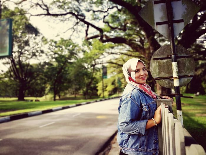 Portrait of mid adult woman wearing hijab standing on road against trees in park