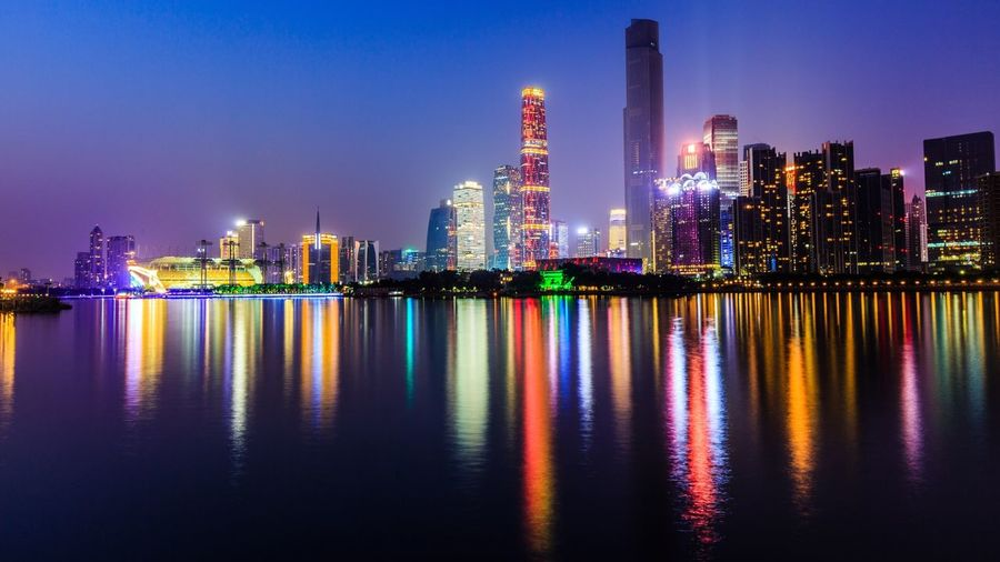 Illuminated cityscape reflecting in pearl river against sky at night