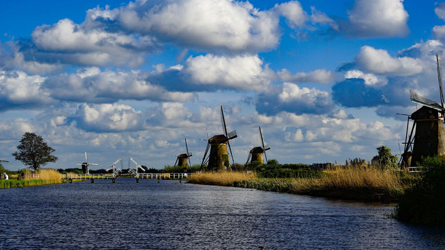 Traditional windmill on field by river against sky