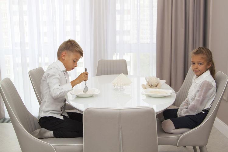 Cute sibling sitting at dining tablet at home