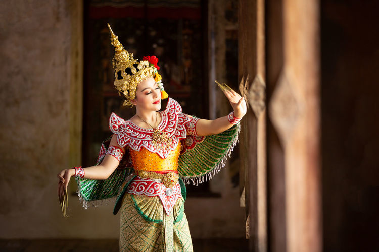 Young woman wearing traditional clothing dancing in temple