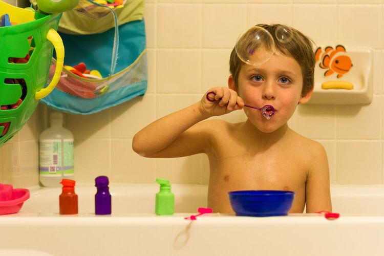 Portrait of shirtless boy in bathroom