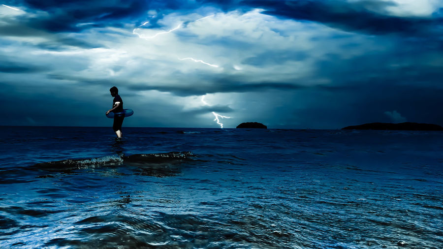 Side view of boy with inflatable ring in sea against thunderstorm cloudy sky
