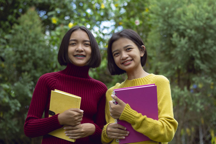 Portrait of smiling teenage girl with friend holding books against trees