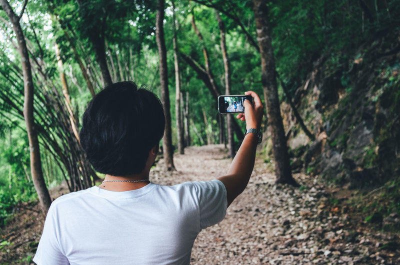 Rear view of man taking selfie while standing on footpath in forest