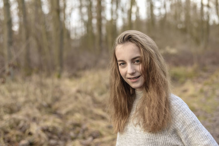 Close-up portrait of teenage girl smiling in forest