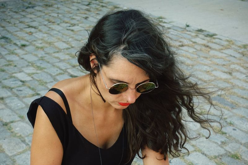 Woman Wearing Sunglasses Sitting On Footpath In City