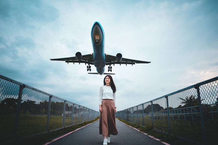 Low angle view of woman standing on airplane against sky