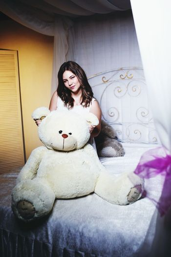 Portrait Of Young Women With Large Teddy Bear On Bed