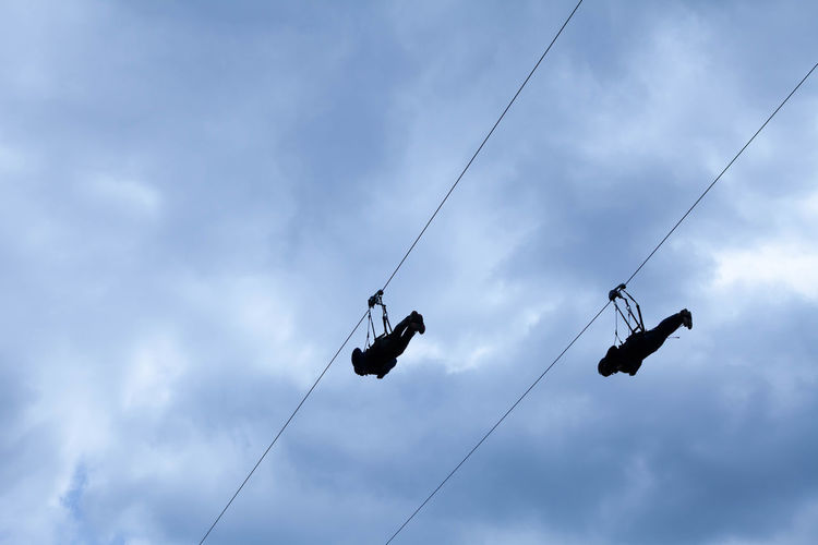 Gigaswing with two people captured @ Rappbodetalsperre, 2018-05-19 Adventure Bungee Cable Cloud - Sky Communication Day Export Extremsport EyeEm EyeEmNewHere Full Length Group Of Animals Hanging Leisure Activity Low Angle View Menschen Nature Outdoors People Real People Rope Seilbahn Seile Sign Silhouette Sky Stahlseil Two People Wolken Wolkig The Traveler - 2018 EyeEm Awards