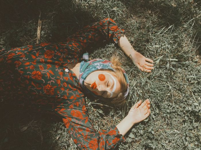 High angle view of woman with make-up lying on field