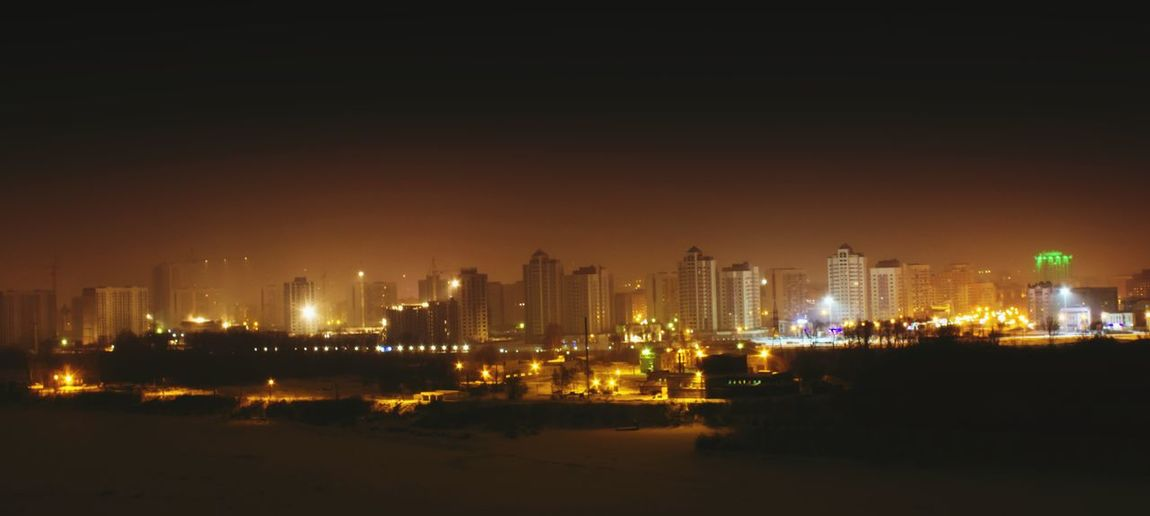 Panoramic shot of illuminated cityscape against clear sky at night