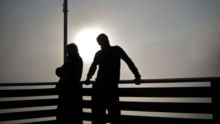 Silhouette of people on railing against sky