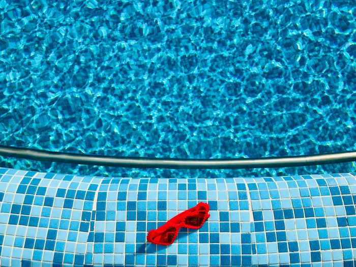 High angle view of red sunglasses at poolside