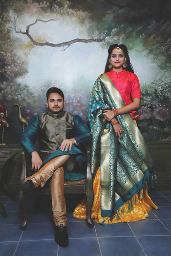 Portrait of young couple in traditional indian attire standing against a designed wall