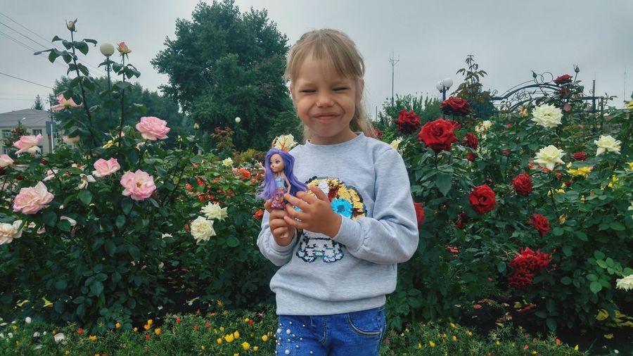 Full length of girl holding flowering plants