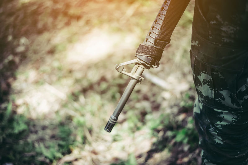Aggression  Close-up Day Equipment Field Focus On Foreground Holding Land Metal Midsection Military Nature One Person Outdoors Plant Protection Real People Selective Focus Standing Weapon