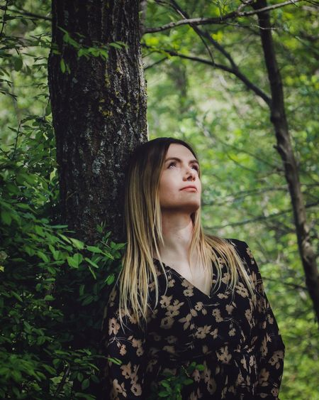 Beautiful young woman standing by tree trunk in forest
