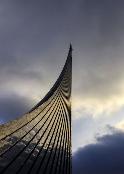 Low angle view of modern built structure against cloudy sky